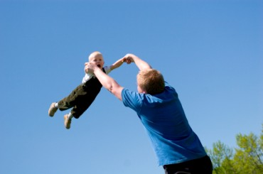 Father Swinging Child Around in the Air
