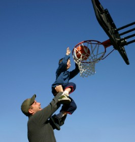 Father Lifting Son Up to the Basketball Hoop