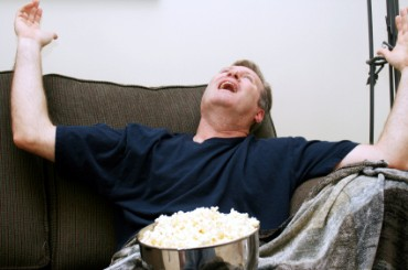 Man Sitting on Couch Watching Football