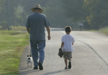 Grandfather and Grandson Walking with the Dog