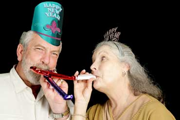 Couple Blowing Noisemakers on New Year's Eve