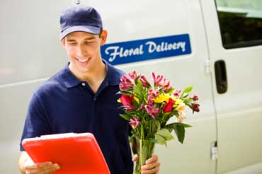 Young Worker Delivery Flowers and Standing in Front of a Delivery Van