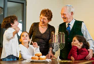 Jewish Grandparents and Grandchildren with a Menorah, Gelt, and Jelly Donuts