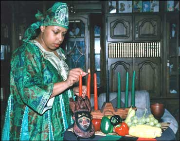 Woman Wearing a Uwole and Lighting Candles in a Kinara