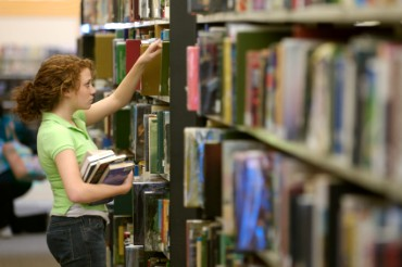 Woman Getting a Book from the Library Shelf