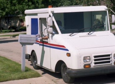 Postal Worker Delivering Mail in Mail Truck