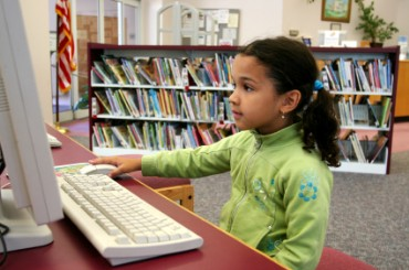 Young Girl Using a Computer in the Library